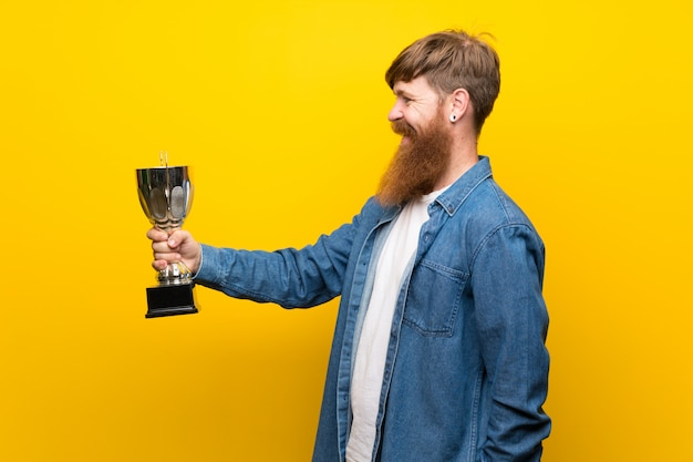 Redhead man with long beard over isolated yellow wall holding a trophy