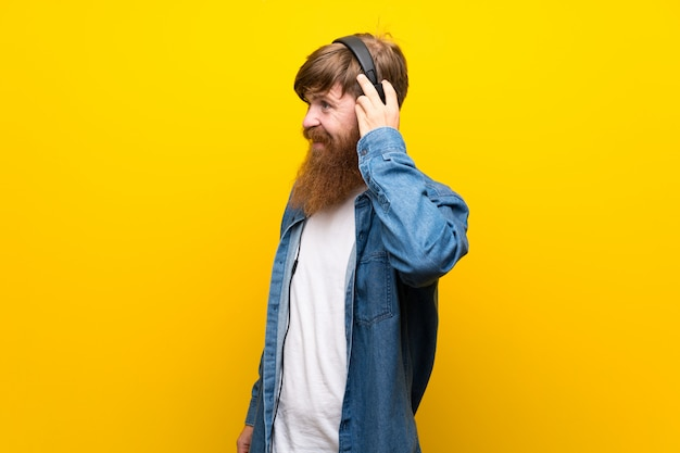 Redhead man with long beard over isolated yellow wall listening to music with headphones