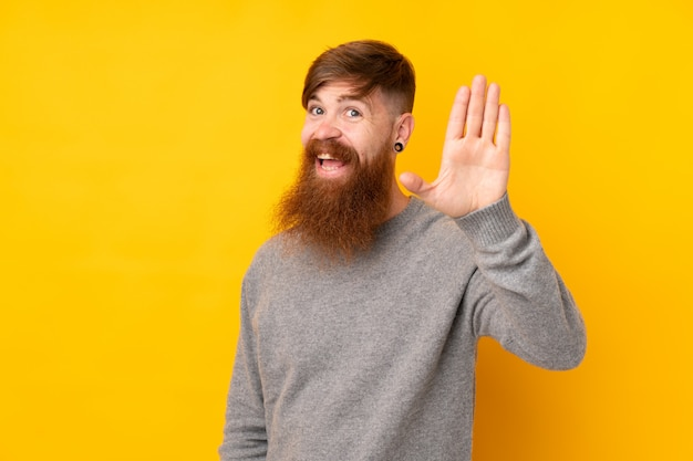 Redhead man with long beard over isolated yellow wall saluting with hand with happy expression
