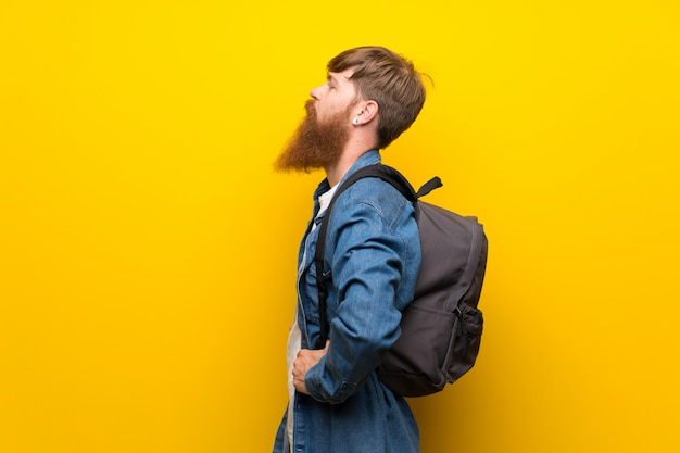 Redhead man with long beard over isolated yellow wall with backpack