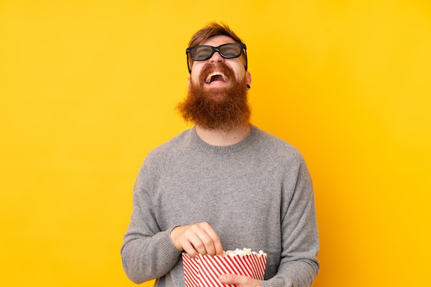 Redhead man with long beard over isolated yellow with 3d glasses and holding a big bucket of popcorns