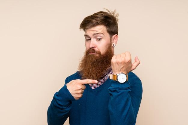 深刻な表情で手の時計を示す孤立した背景に長いひげを持つ赤毛の男
