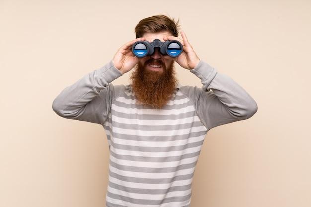 黒双眼鏡で孤立した背景に長いひげを持つ赤毛の男