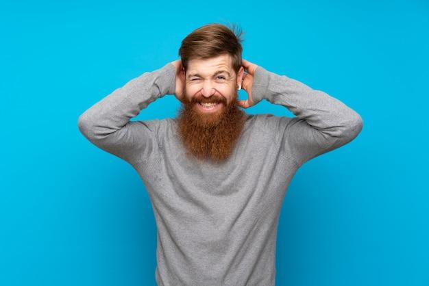 孤立した青い欲求不満の長いひげを持つ赤毛の男と頭の上の手