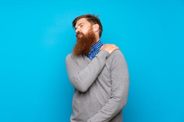 努力をしたために肩の痛みに苦しんでいる孤立した青の上の長いひげを持つ赤毛の男