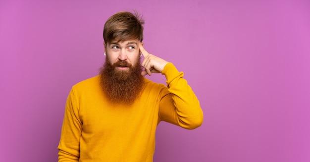 Рыжий мужчина с длинной бородой на изолированных фиолетовый делает жест безумия, положив палец на голову