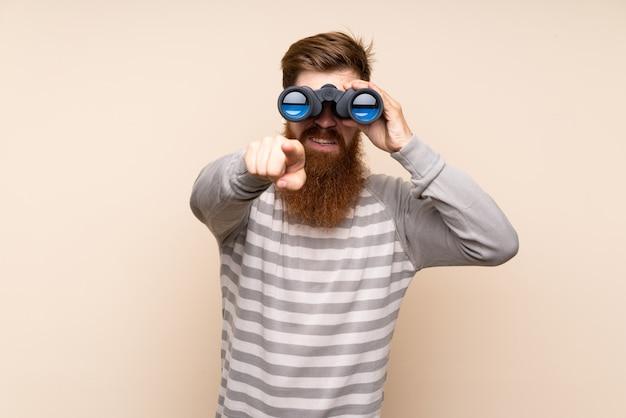 黒双眼鏡で孤立した壁の上の長いひげを持つ赤毛の男