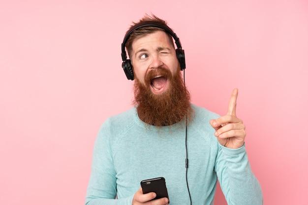 Рыжий мужчина с длинной бородой над розовой стеной слушает музыку с мобильного и поет