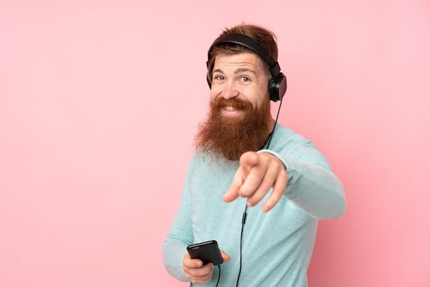 Рыжий мужчина с длинной бородой на розовой стене слушает музыку