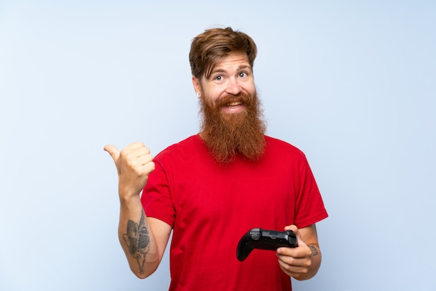 Redhead man with long beard playing with a video game controller pointing to the side to present a product