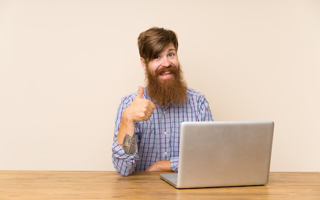 Redhead man with long beard in a table with a laptop giving a thumbs up gesture