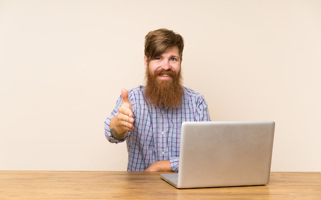Redhead man with long beard in a table with a laptop handshaking after good deal