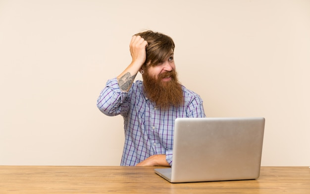 Redhead man with long beard in a table with a laptop having doubts and with confuse face expression