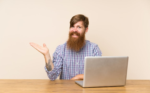 Redhead man with long beard in a table with a laptop holding copyspace imaginary on the palm