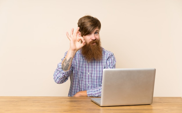 Redhead man with long beard in a table with a laptop showing an ok sign with fingers
