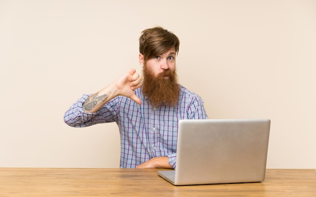 Redhead man with long beard in a table with a laptop showing thumb down sign