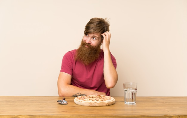Redhead man with long beard in a table and with a pizza having doubts and with confuse face expression
