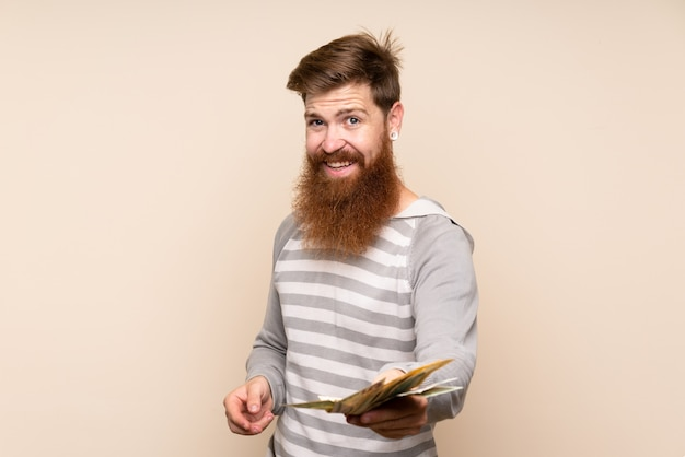 Redhead man with long beard taking a lot of money