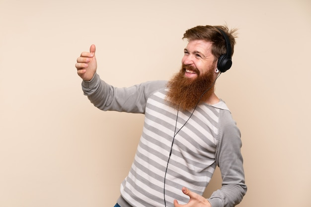 Redhead man with long beard using the mobile with headphones and dancing