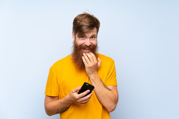 Redhead man with long beard with a mobile over  blue wall smiling a lot
