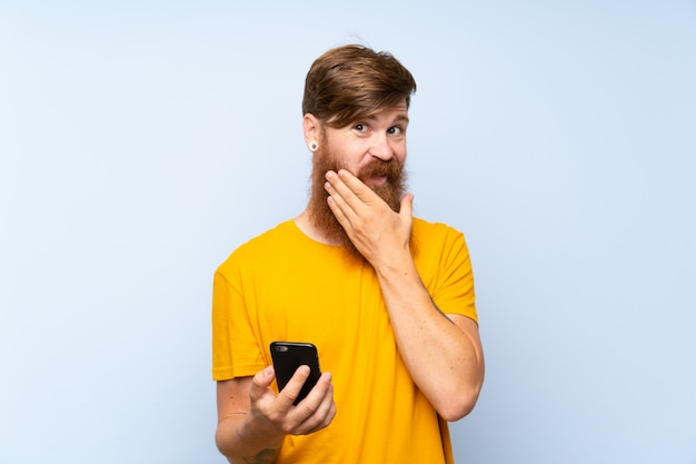 Redhead man with long beard with a mobile over  blue wall thinking an idea