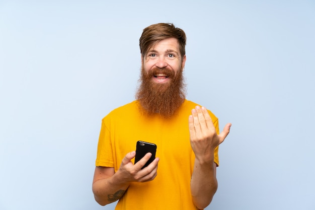 Redhead man with long beard with a mobile over isolated blue wall inviting to come with hand. happy that you came