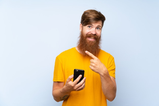 Redhead man with long beard with a mobile over isolated blue wall pointing to the side to present a product