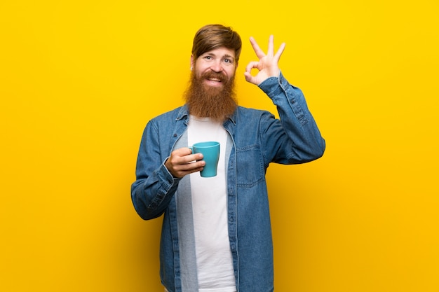 Redhead man with long beard over  yellow wall holding hot cup of coffee