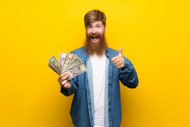 Redhead man with long beard over  yellow wall taking a lot of money