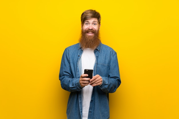 Redhead man with long beard over  yellow wall using mobile phone