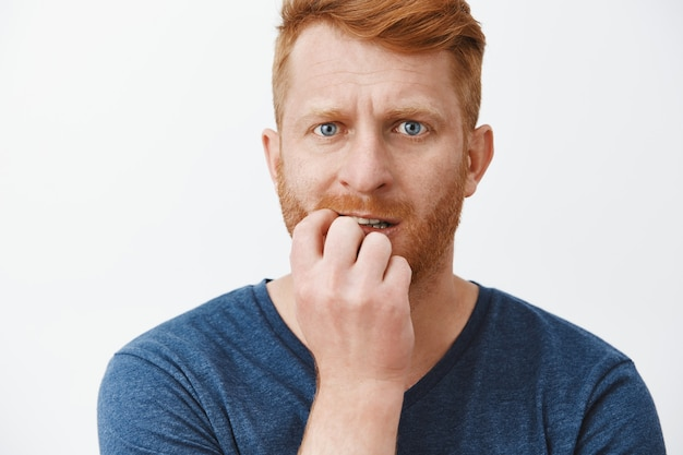 Redhead man worried, feeling scared, biting fingernails and staring nervously, feeling anxious