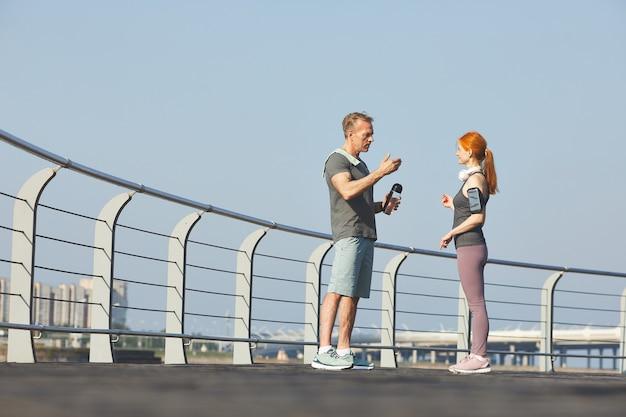 Рыжая зрелая женщина со смартфоном на руке планирует тренировку на свежем воздухе с фитнес-инструктором, пока они разговаривают на набережной