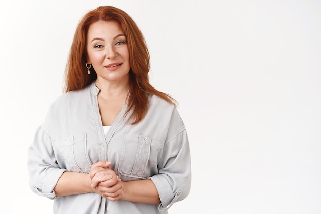 Redhead middle-aged beautiful woman taking emotions control trying stay confident speaking front large audience hold hands together chest smiling friendly speaking self-assured white wall