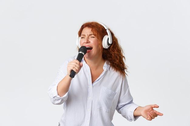 Рыжая женщина средних лет наслаждается пением эмоционального караоке, держит микрофон и в наушниках