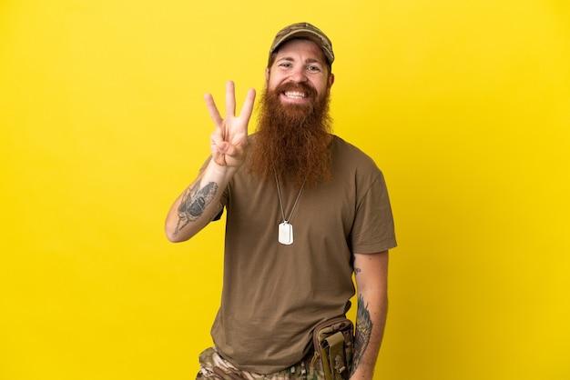 黄色の背景に分離されたドッグタグを持つ赤毛の軍人は幸せで、指で3を数えます
