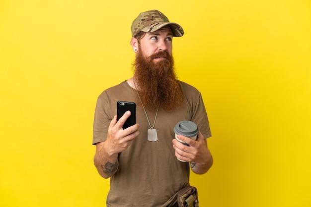 Рыжий военный с собачьей биркой на желтом фоне держит кофе на вынос и мобильный, думая о чем-то
