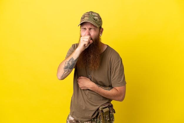 Рыжий военный с собачьей биркой на желтом фоне страдает от кашля и плохо себя чувствует