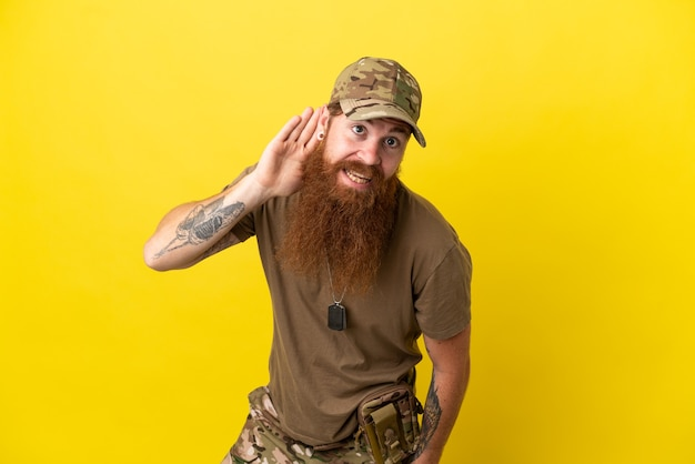 Рыжий военный с собачьей биркой на желтом фоне слушает что-то, положив руку на ухо