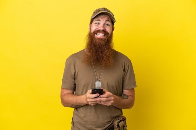 黄色の背景に分離されたドッグタグを持つ赤毛の軍人が携帯電話でメッセージを送信します