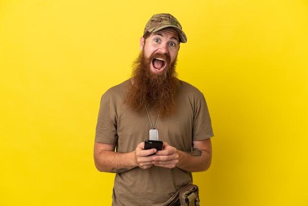 Рыжий военный с собачьей биркой на желтом фоне удивлен и отправляет сообщение