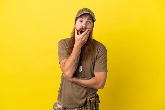 Рыжий военный с собачьей биркой на желтом фоне удивлен и шокирован, глядя вправо