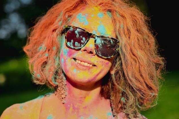 공원에서 화려한 페인트로 덮여 곱슬 머리를 가진 빨간 머리 모델