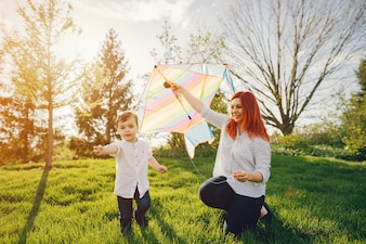 redhead mom in a white blouse playing with her little sweet son i