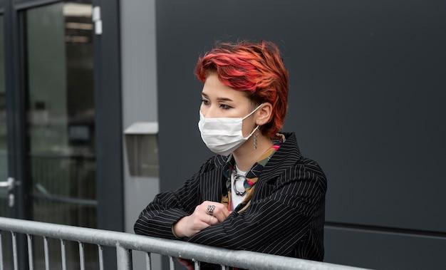 Рыжий небинарный человек в медицинской маске на улице