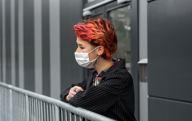Redhead non binary person wearing a medical mask outdoors