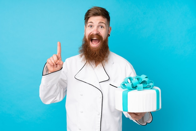Redhead pastry chef with long beard holding a big cake over isolated blue wall pointing up a great idea