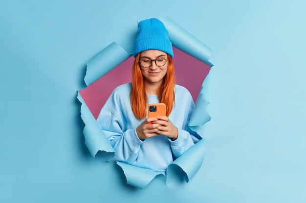 Redhead pleased young caucasian woman uses mobile phone types sms message surfs in social networks wears blue hat and sweatshirt.