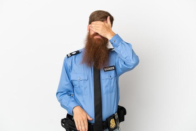 Рыжий полицейский, изолированные на белом фоне, закрывая глаза руками. не хочу что-то видеть