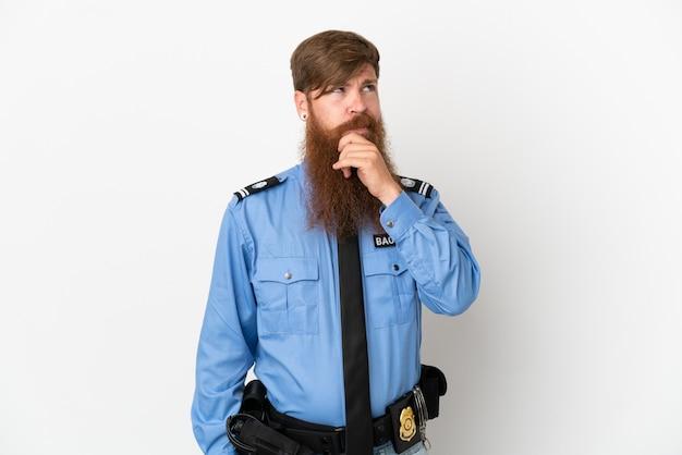 疑いを持って、混乱した表情で白い背景に孤立した赤毛の警官