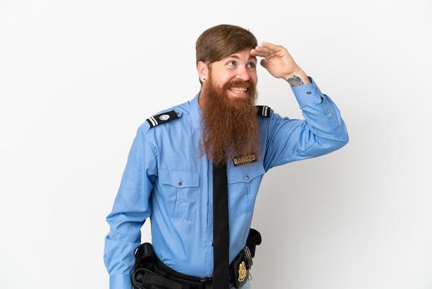 흰색 배경에 격리된 빨간 머리 경찰은 무언가를 보기 위해 손으로 멀리 바라보고 있습니다.